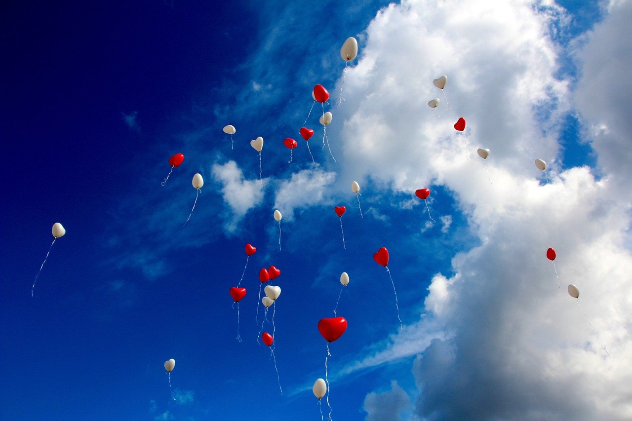 A photo of heart-shaped balloons in the air.